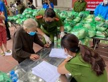 Chiến sĩ công an và đoàn viên thanh niên quận Hoàng Mai phát quà từ thiện cho người dân