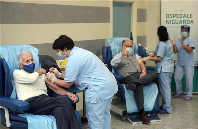 Nhân viên y tế tiêm chủng vaccine ngừa COVID-19 cho người dân tại Milan, Italy, ngày 27/12/2020 (Ảnh: AFP/TTXVN)