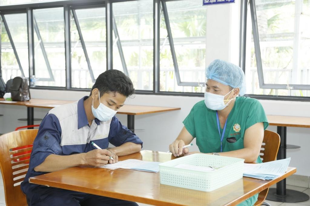 Các nhân viên y tế tư vấn kỹ càng cho các công nhân trước khi tiêm vaccine.