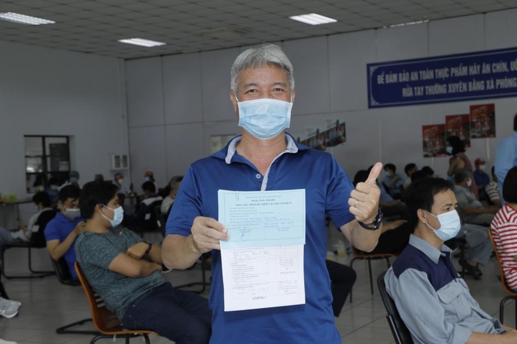 Người lao động vui mừng khi vừa hoàn thành thành mũi 1 vắc-xin ngừhf máy vui mừng sau khi hoàn
