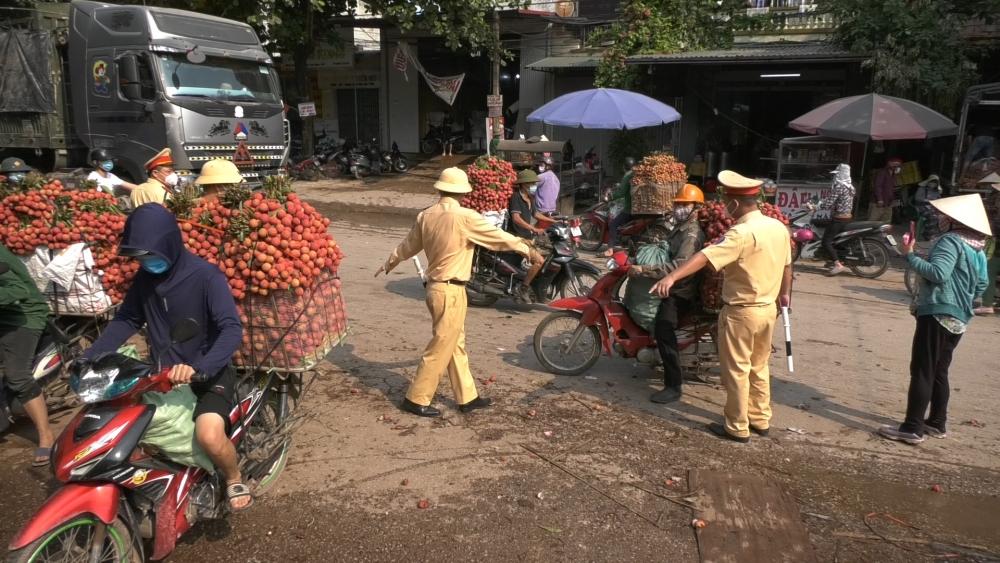 """CSGT Bắc Giang """"đội nắng"""" phân luồng giao thông, đẩy xe vải cho người dân"""