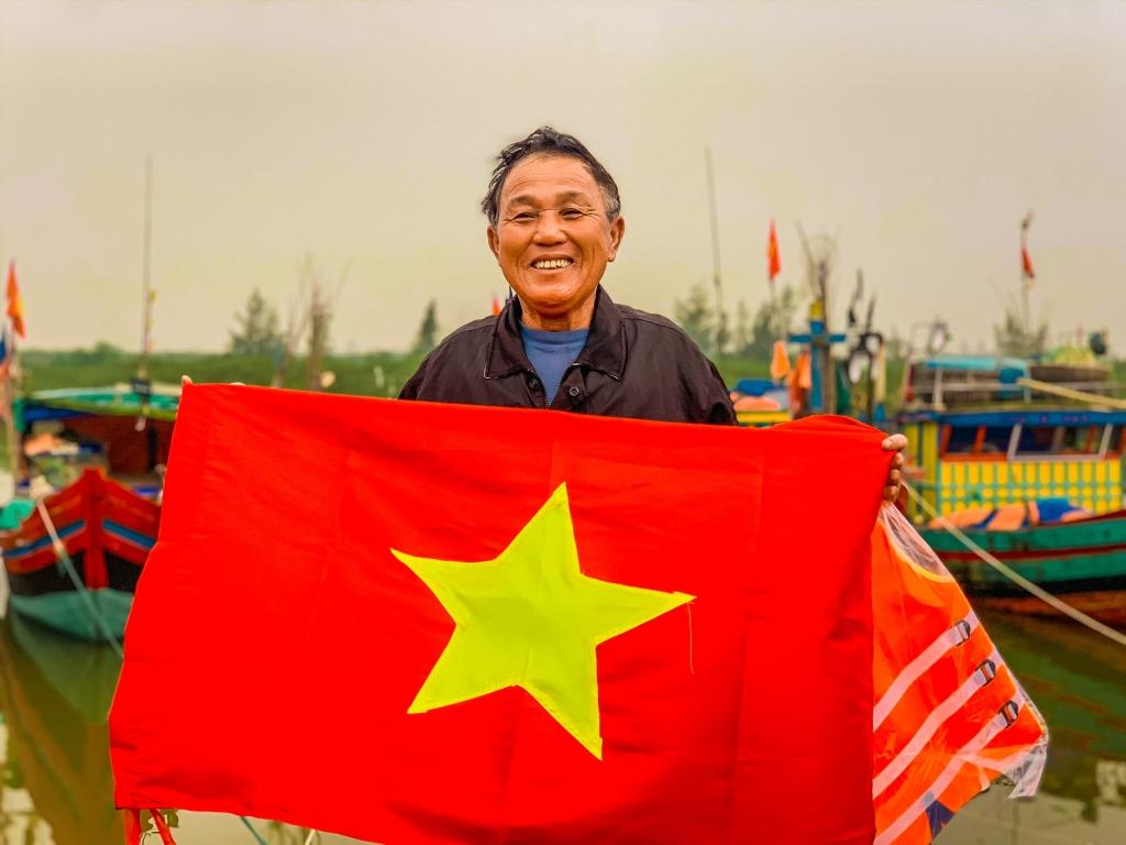 Nụ cười rạng rỡ của ngư dân tại cảng cá Lộc Hà, tỉnh Hà Tĩnh khi nhận món quà là những lá cờ Tổ quốc