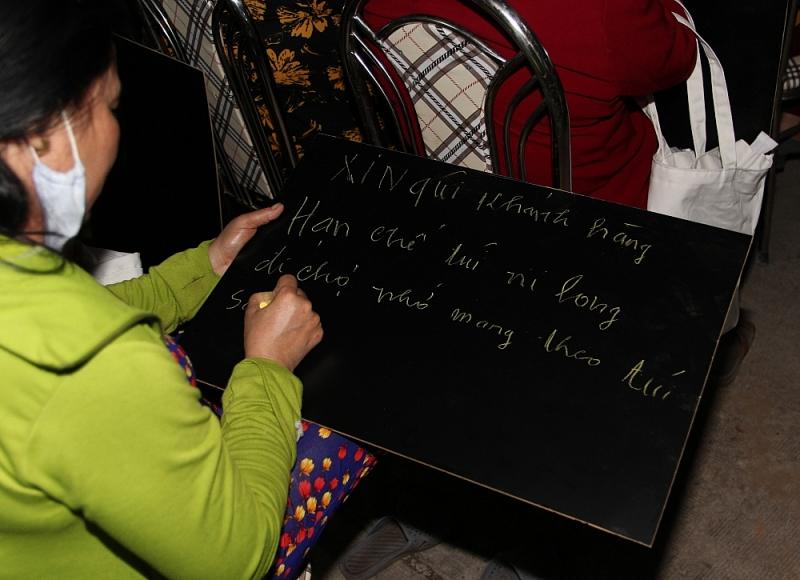 Tiểu thương viết lời kêu gọi hạn chế dùng túi ni lông tại sự kiện.