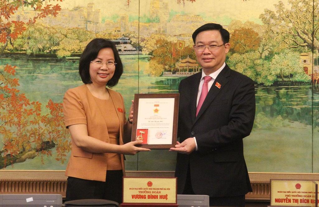Trưởng đoàn đại biểu Quốc hội thành phố Hà Nội Vương Đình Huệ trao Kỷ niệm chương cho đại biểu Bùi Huyền Mai.