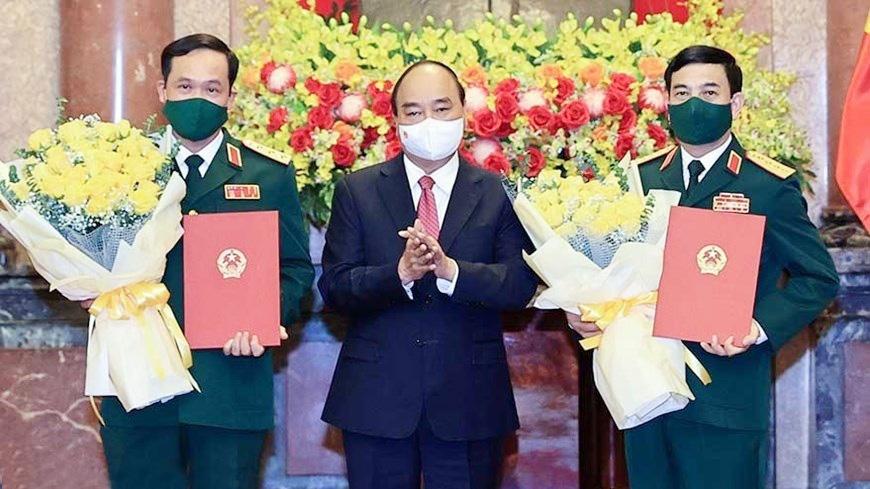 Chủ tịch nước Nguyễn Xuân Phúc trao quyết định thăng quân hàm, hoa chúc mừng Bộ trưởng Quốc phòng Phan Văn Giang (phải) và Thứ trưởng Vũ Hải Sản.