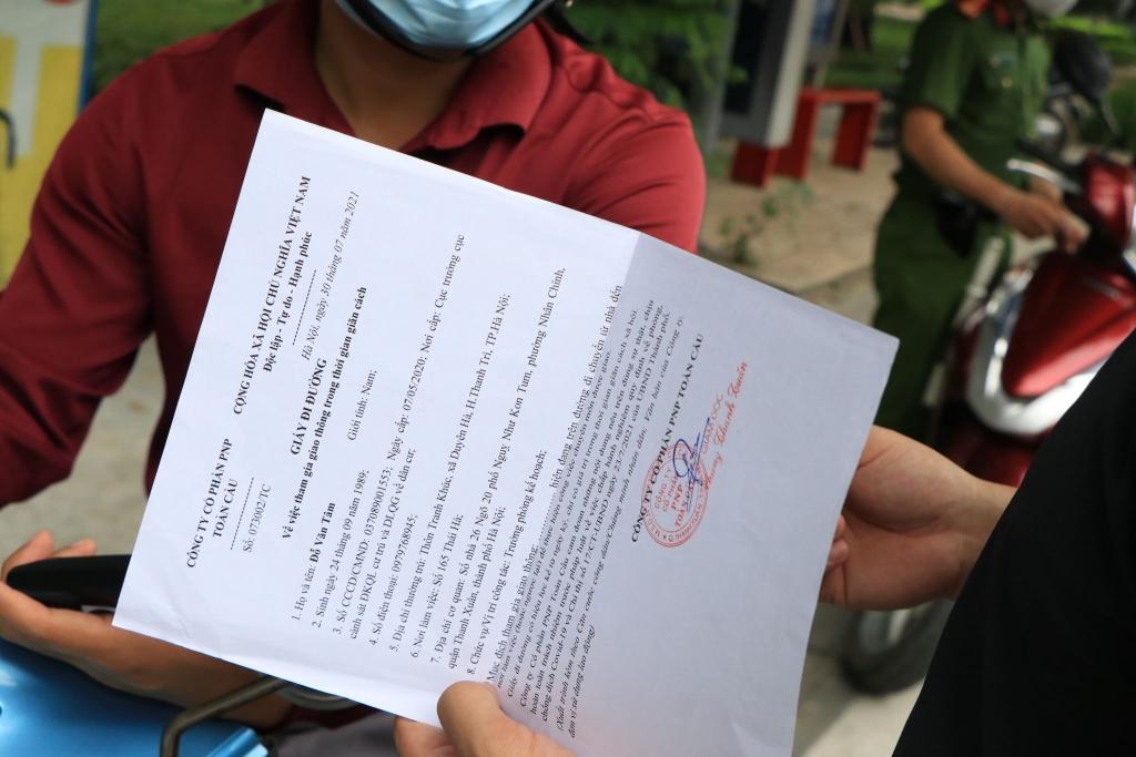 Thành viên tổ công tác kiểm tra giấy đi đường của người qua chốt