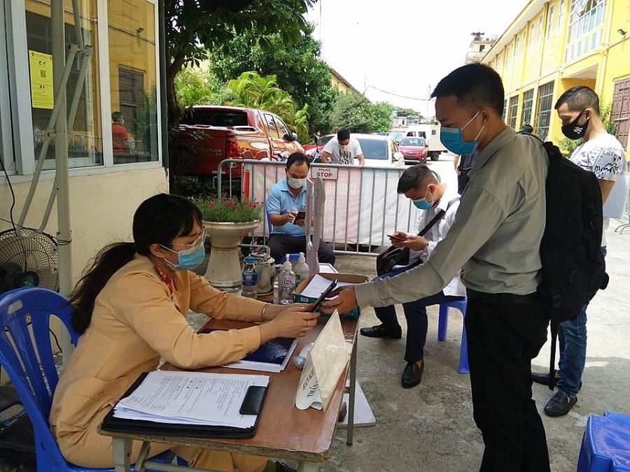Người dân đến làm thủ tục đăng ký mới phương tiện được nữ cảnh sát giao thông hướng dẫn khai báo y tế ngay từ ngoài cổng