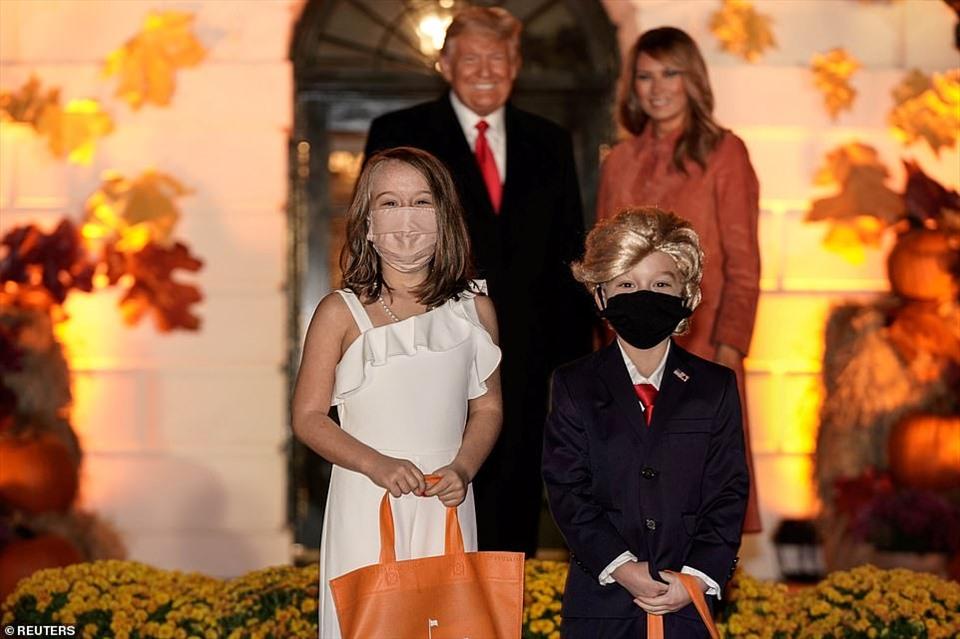 Hai trẻ hóa trang thành vợ chồng Tổng thống Donald Trump và phu nhân chụp ảnh cùng ông Donald Trump và bà Melania Trump tại một lễ kỷ niệm Halloween ở Nhà Trắng. Ảnh: