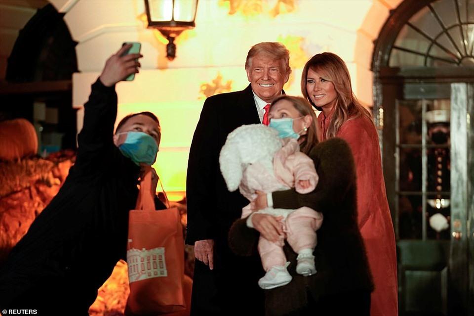 Vợ chồng tổng thống Mỹ chụp ảnh cùng 1 gia đình. Họ giữ khoảng cách xa khi chụp ảnh để đảm bảo giãn cách xã hội trong bối cảnh đại dịch COVID-19. Ảnh: