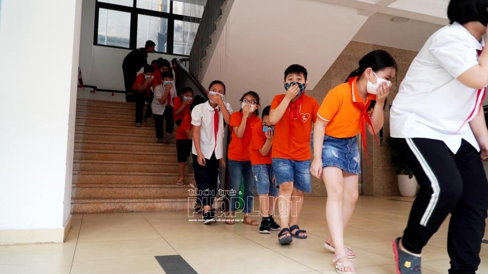 Học sinh các lớp được hướng dẫn di chuyển thấp người tới khu vực an toàn