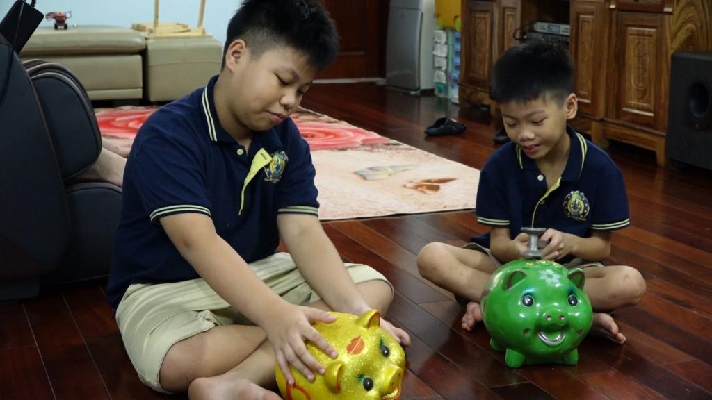 Hai em thiếu nhi Nguyễn Đức Anh lớp 6a4 trường THCS Xanh Tuệ Đức và em Nguyễn Huy Hiếu đập lợn đất để ủng hộ Quỹ Vaccine phòng chống dịch Covid-19