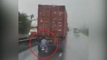 Nam thanh niên đi xe máy núp sau container để tránh mưa