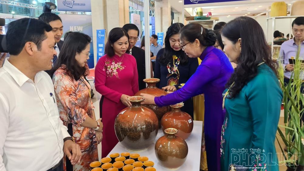 Bà Nguyễn Thị Tuyến - Phó Bí thư Thành ủy, Trưởng ban Dân vận Thành ủy Hà Nội (áo dài hồng) cùng các đại biểu tham quan gian hàng của nghệ nhân tại hội chợ