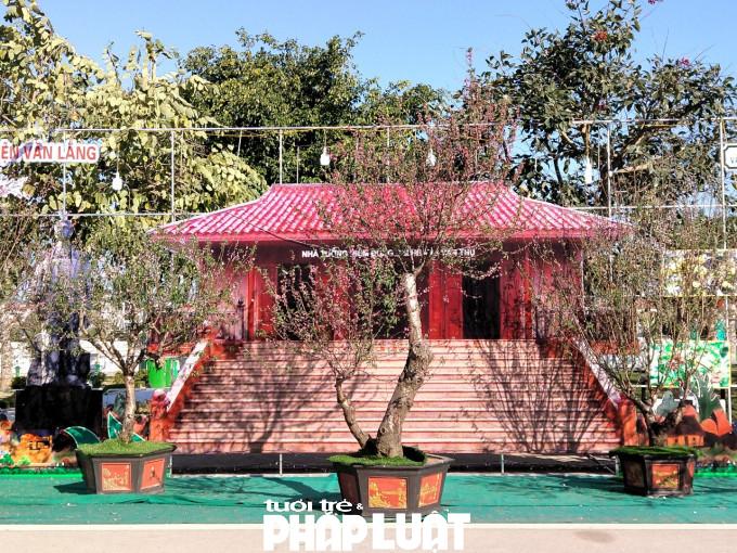 Không gian trưng bày có mô hình Nhà tưởng niệm anh hùng dân tộc, trước cửa là những cây đào héo rũ, hoa đã khô quắt.