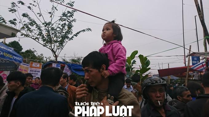 Một em bé được bố đưa đi hội chợ