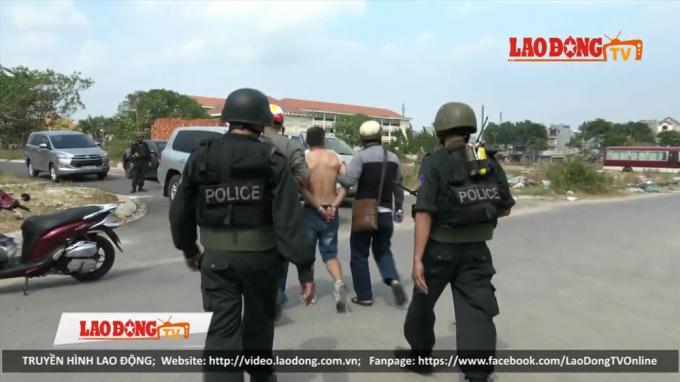 Cảnh sát áp tải một đối tượng trong đường dây ma túy do Wu Hao Shan cầm đầu