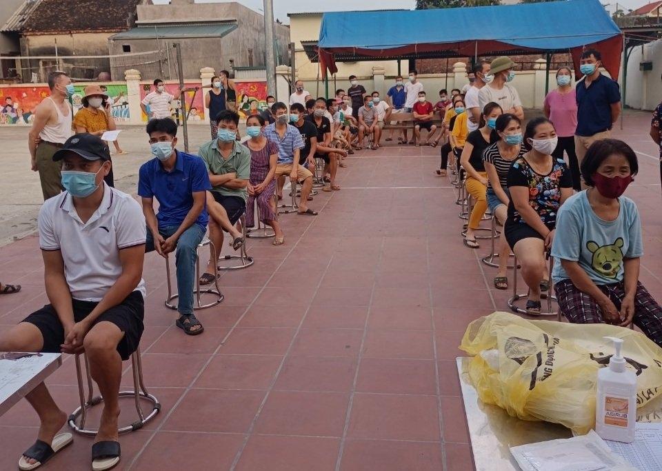 Người dân trong thôn được hẹn giờ, ngồi đảm bảo khoảng cách phòng chống dịch