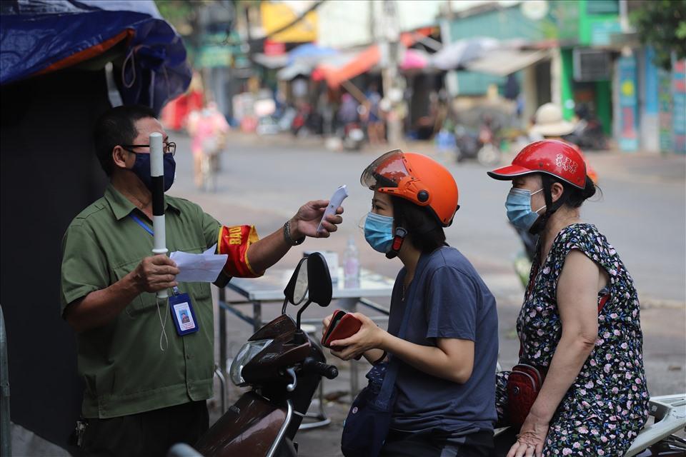 Người dân đến chợ phải được đo thân nhiệt, có phiếu đi chợ hợp lệ.